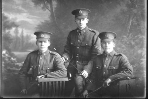 3/4 portrait of three Dibble brothers, Corporal (later Sergeant) Ralph Ambrose Dibble, Reg no 26572 (centre), and Privates Jesse Cyril Dibble(right), Reg No 26571, and Victor Thomas Dibble (left), Reg No 26573, all of the New Zealand Rifle Brigade, 8th Reinforcements to the 4th Battalion, - H Company, 17th Reinforcements.